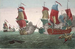 From the left, in the background three sailing warships at sea, one clearly flying a British naval ensign; in the center-right foreground, three sailing warships, two of them firing broadsides with gun smoke starting to cover them up. There was no US flag on the American ship, so the British said John Paul Jones was a pirate.