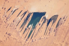 This astronaut photograph features one of the largest of a series of ten mostly fresh water lakes in the Ounianga Basin in the heart of the Sahara Desert of northeastern Chad.