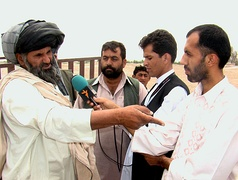 A reporter interviews a man in Helmand Province, Afghanistan, 2009.