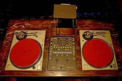 Vintage DJ Station. A DJ mixer is placed between the two turntables.