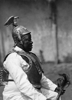 A Cameroonese tribal chief wearing German helmet, armour, and uniform in British Cameroons, during a funeral. This photograph was sought out and used by the Nazis in propaganda to show the existence of German culture in the ex-German colony to justify a return of Germany's lost colonies.