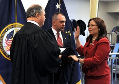 Duckworth being sworn in as Assistant Secretary of Public and Intergovernmental Affairs for the United States Department of Veterans Affairs, by Judge John J. Farley with her husband Bryan Bowlsbey beside her