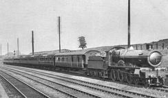 A black and white picture of four railway lines in a shallow cutting, a large steam engine leads a train of coaches from middle-left to right-foreground
