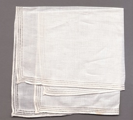 A linen handkerchief with drawn thread work around the edges