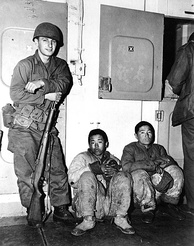 A US Marine guards North Korean prisoners of war aboard an American warship in 1951.