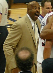 A man, wearing a brown suit and white shirt, is shouting while standing on a basketball court, surrounded by several other people.