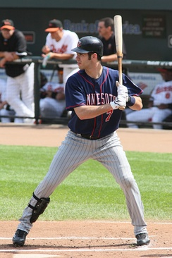 A man in a left-handed batting stance wearing pinstriped gray pants, a black shinguard on his right leg, a dark blue baseball jersey, and a dark-colored batting helmet.
