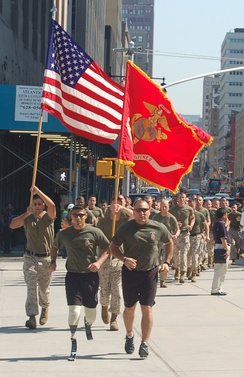 A United States Marine with bilateral prosthetic legs leads a formation run