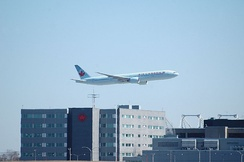 An Air Canada flight flies past the company's corporate headquarters, located at Montréal–Trudeau International Airport.