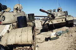 Two Iraqi tanks lie abandoned near Kuwait City on 26 February 1991.