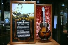 Carter's Gibson guitar, accompanied by a photograph of Carter at the Country Music Hall of Fame