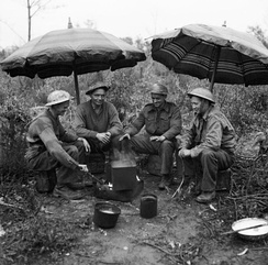 Gunners of the 78th Field Regiment, Royal Artillery make use of two sunshades from a cafe to keep the rain off while making a brew, Anzio, Italy, 27 February 1944.