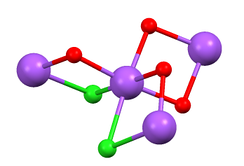 Coordination sphere of Na+ in the metastable dihydrate of sodium chloride (red = oxygen, violet = Na+, green = Cl−, H atoms omitted).[2]