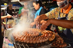 Sai krok Isan being freshly grilled at a market in Uttaradit, Thailand