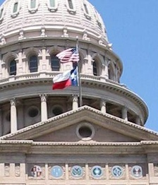 The U.S. and Texas flags at the Texas State Capitol.