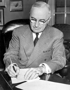 President Truman signing a proclamation declaring a national emergency and authorizing U.S. entry into the Korean War