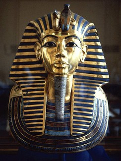The iconic gold burial mask of Tutankhamun, inlaid with turquoise, lapis lazuli, carnelian and coloured glass.
