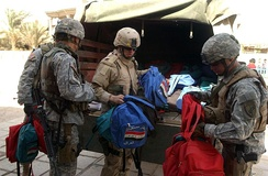 345th PSYOP Company (pictured left to right: SPC Jeffrey A. Cogbill, SPC William O'Connell, CPL Ryan Lewis), United States Army Reserve, hand out school supplies in Baghdad, Iraq, 2005.