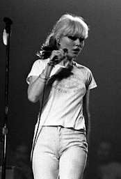 Singer Debbie Harry is shown onstage at a concert. She is wearing jeans and a T-shirt.
