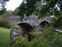 A three-arch bridge spanning a river, surrounded by trees