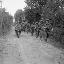 A motorcycle and infantry of the 2nd Battalion, Glasgow Highlanders, 46th Infantry Brigade, 15th (Scottish) Infantry Division, advance along a lane near Caumont, 30 July 1944.