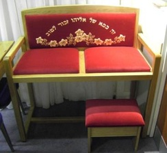 """Chair of Elijah"" used during the brit milah (circumcision) ceremony. The Hebrew inscription reads ""This is the chair of Elijah, remembered for Good."""