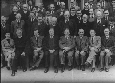 Photo taken at DIAS in 1942First row from left:  Sheila Tinney, Pádraig de Brún, Paul Dirac, Éamon de Valera, Arthur W. Conway, Arthur Eddington, Erwin Schrödinger, Albert Joseph McConnell