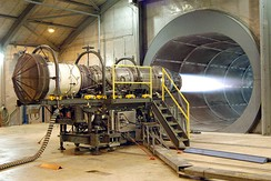 A fighter jet engine undergoing testing. The tunnel behind the engine allows noise and exhaust to escape.