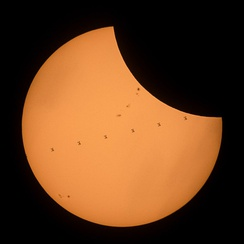 A composite image showing the ISS transit of the Sun while the 2017 solar eclipse was in progress.