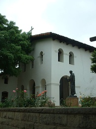 The entrance lobby and belfry of the Mission San Luis Obispo de Tolosa. A statue of Fray Junípero Serra stands outside the church.