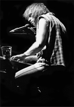 Black-and-white photo of a man playing the piano, there is a drink on the piano.