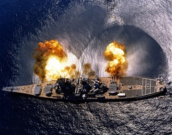 USS Iowa fires a full broadside of her nine 16″/50 and six 5″/38 guns during a target exercise