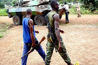 Armed Ivorians next to a French Foreign Legion armoured car, 2004