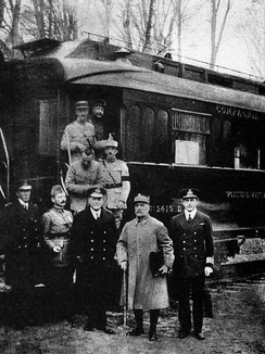 black and white photograph of five men in military uniforms standing side-to-m right, seen outside his railway carriage No. 2419 D in the Forest of Compiègne.