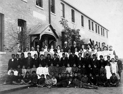 Posed, group photo of students and teachers, dressed in black and white, outside a brick building in Regina, Saskatchewan