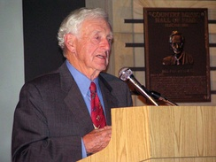 White-haired elderly gentleman in suit and tie speaks at a podium.