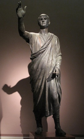"The Orator, c. 100 BC, an Etrusco-Roman bronze sculpture depicting Aule Metele (Latin: Aulus Metellus), an Etruscan man of Roman senatorial rank, engaging in rhetoric. He wears senatorial shoes, and a toga praetexta of ""skimpy"" (exigua) Republican type.[5] The statue features an inscription in the Etruscan alphabet"