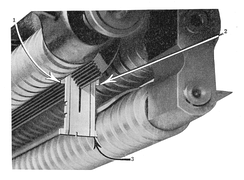 The linotype distributor rail with a matrix hanging from it. The three screws move the matrix along the rail until it drops into the correct magazine channel.