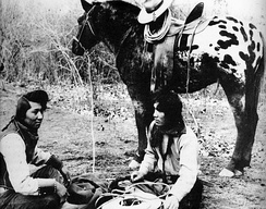 In the foreground, two Native American men wearing cowboy attire sit crosslegged on the ground. In the background, a dark colored horse with a white and black spotted rump stands saddled and bridled.