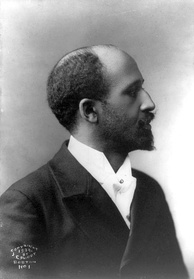 A formally dressed African American man, sitting for a posed portrait