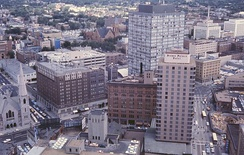 Downtown Denver cityscape, 1964. Includes Denver's oldest church (Trinity United Methodist), first building of the Mile High Center complex, Lincoln Center, old brownstone part of the Brown Palace Hotel, and Cosmopolitan Hotel – since demolished.