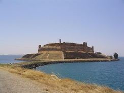 A large ruinous castle with concentric walls and towers located on an island that is connected to the shore by a causeway