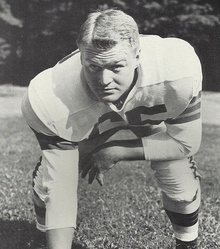 Posed photograph of Noll in a football uniform without a helmet in a three-point stance