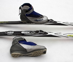Cross-country ski boot and standardized binding system for classic skiing. The skier clicks the toe of the boot into the binding and releases with the button in front of the boot.
