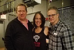 "Three people stand in a gray lobby area; on the left, a man in a black sweater and pink button down shirt, to his right, a woman in a black tank top that reads ""THEATER OF THE APES"", and to her right, a man with glasses in a black and white plaid shirt."