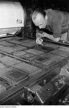 A printer inspecting a large forme of type on a cylinder press. Each of the islands of text represents a single page, the darker blocks are images. The whole bed of type is printed on a single sheet of paper, which is then folded and cut to form many individual pages of a book.