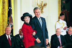 Photograph of President George W. Bush stands with Rita Moreno
