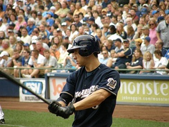 Ryan Braun, wearing a dark blue Brewers uniform, yields a baseball bat