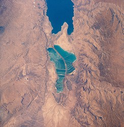 View of salt evaporation pans on the Dead Sea, taken in 1989 from the Space Shuttle Columbia (STS-28). The southern half is separated from the northern half at what used to be the Lisan Peninsula because of the fall in level of the Dead Sea.
