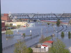 A street with a major amount of water on it due to flooding. A bridge is on the top of the image, and a row of buildings to the left. Sandbags are in front of the buildings
